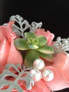 Coral roses, succulent, dusty miller and pearl accents.