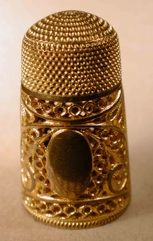 The supporting, thicker, wires were often shaped in a Paisley pattern that is said to have originated in India and symbolizes the 'seed of life'.  These thimbles often incorporated an 'oval' or shield for engraving an owners initials or crest