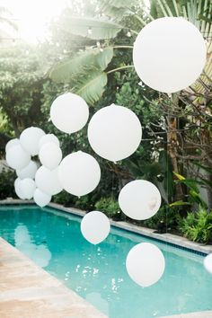 Elegant and chic backyard pool party. Decorate using white balloons for a classic summer look.
