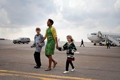First Lady Michelle Obama walks across the tarmac with Megan Soukup, 9, and Joseph Hudella, 10, participants in the Defending the Blue Line program, as she prepares to greet military families at Minneapolis-St. Paul International Airport in Minneapolis, Minn., March 16, 2012. The First Lady traveled to Minnesota to meet with National Guard families and local community leaders dedicated to supporting military families. (Official White House Photo by Sonya N. Hebert)