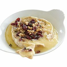 Warm Cranberry-Walnut Brie Recipe  1. Preheat oven to 350°.  2. Using a serrated knife, remove topmost rind from cheese; discard rind. Place cheese, cut side up, in a small ovenproof baking dish; sprinkle with cranberries and thyme. Top evenly with nuts. Bake at 350° for 15 minutes or until cheese is soft and warm. Serve immediately with crackers.