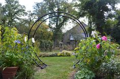 """$375 Moon Gate Arch - wouldn't this be wonderful with roses on it? Our arches are made with graceful curves of tubular steel, powder coated black. 84"""" tall in center, 89"""" wide, 20"""" front to back, 47 ½"""" outside across base, 40"""" inside. Includes 4 x 18"""" ground spikes to anchor base plates."""