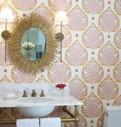 Modern colorful powder room with pink and orange lotus wallpaper from Galbraith and Paul; Arteriors Home modern spikey brass oval mirror; Urban Electric brass wall sconces; unlacquered brass washstand; carrara marble vanity top; brass in the bath