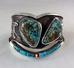 """Preston Monongye Cast Silver Bracelet - A man sized bracelet by the Master Hopi silversmith Preston Monongye is tufa cast silver with a Peyote Bird and Peyote symbols. Set with two large Royston turquoise and finished with a bar of inlay: turquoise, coral, ivory and jet. This impressive bracelet is over 2"""" tall, the interior measures a little over 6"""" plus the gap of 1 1/4"""". Very heavy."""