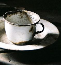 Enamel cup.  What simplicity.  Lovely composition in this photo.   Have many enamel cups...need to rust them up!