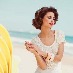 Red lips, curls and lace by the beach.