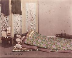 A studio photo of two women sleeping in wadded futon bedding with their heads on wooden head supports. It must be Winter as they use two layers for both mattress and cover. There is an ando lamp near their heads. A folding screen illustrated with flowers and birds stands behind it. Near their feet is a hakohibachi (brazier encased in a wooden box) with a tetsubin (iron hot water kettle).