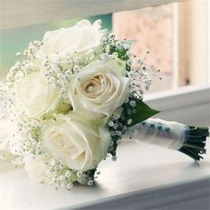 Beautiful white roses and baby's breath with white tulle wrapping the stems and colored floral pins accenting the white, this is very romantic.