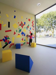 LOVE THIS,,, BOTH THE SHAPES ON WALL, BRIGHT AND EYE-CATCHING, AND THE FOAM CUBES FOR SEATING AS WELL!!!!   Anansi Playground Building by Mulders vandenBerk Architecten - Dezeen