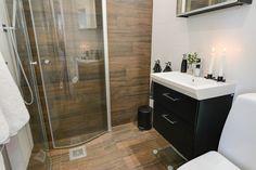 Golvet går upp i en fondvägg i detta stiliga badrum