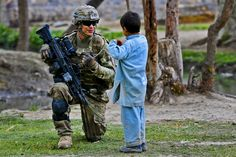 U.S. Army Pfc. Jared Baughn learns Pashtu from an Afghan child while on patrol on Combat Outpost Terezayi in Afghanistan's Khowst province, April 10, 2012. Baughn is assigned to Company C, 1st Battalion, 501st Infantry Regiment. (U.S. Army photo by Spc. Eric-James Estrada)
