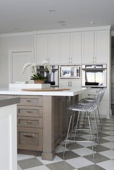 Grey and white chequered floor with grey work tops wooden surface and white glossy brick surround up stand
