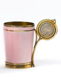 A jewelled, silver-gilt and guilloché enamel cup by Fabergé, Moscow, 1908-1917, the body enamelled translucent pink over wavy engine-turned ground, the scroll handle set with a cabochon stone and enclosing a silver coin dated 1770.