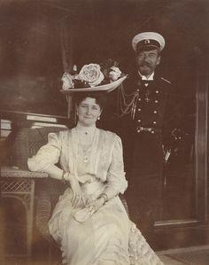 Imperador Nicolau II e a imperatriz Alexandra Feodorovna, sentada na cadeira de cana, ambos sorrindo, a bordo do Yacht imperial Standart, em Reval, Rússia (agora Tallinn, Estónia). Junho de 1908.