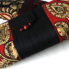 This raw silk clutch with hand-painted Kalamkari art work is made by artisans in South India