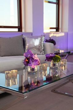 Mercury votive holders and bud vases filled with orchids top a low glass coffee table.