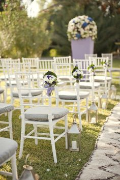 Love these lanterns at the end of each row with small flowers tied to the chairs