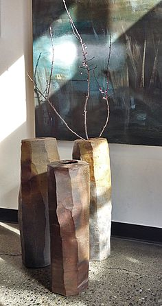 """ERIC GORDER: Faceted Cylinder Vases Elegant faceted cylinder vases make a dramatic display of spring branches. Wood fired in Oregon. This listing is for the set of three but they may be sold separately. Please contact the Gallery for information.  Dimensions/individual prices: 22-1/2"""" tall ($650.00); 26"""" tall ($750.00); and 26"""" tall ($750.00). All 7-1/2"""" in diameter."""