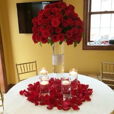 All red roses arrangement perched on top of tall cylinder vase .