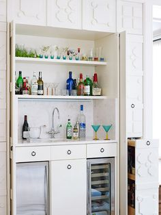 Hide the bar in the kitchen (or in this case the living room) to class it up.  Like the idea of hiding the bar.  Love the cabinet on the right that is holding the liquor bottles
