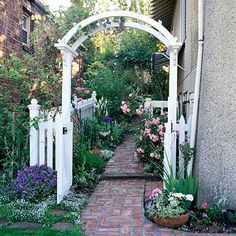 Stuck with a narrow side yard? Use a simple arbor to help make it a destination. Here, an otherwise wasted, long and narrow space becomes a lush, inviting path.