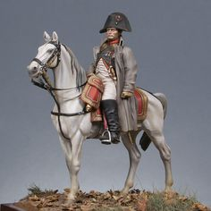 Mounted Napoleon in overcoat.  According to some eyewitnesses, these are the clothes Napoleon wore at his last battle, Waterloo, and indeed, did prefer these to more intricate clothing that many of his officers wore.  He is wearing the uniform of a colonel of Chasseurs of the Guard, and a rather battered gray overcoat, and his favorite bicorne hat.