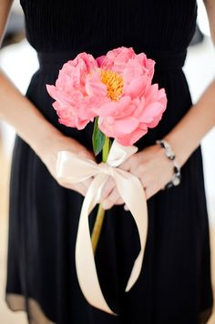A single, stunning, pink peony tied with a silk ribbon creates a sophisticated look.