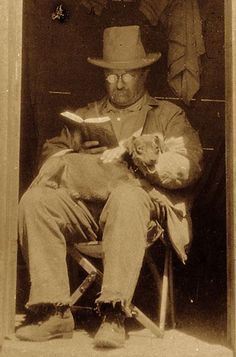 President Theodore Roosevelt reads a book, while his dog Skip rests in his lap, in the doorway of the West Divide Creek ranch house in Colorado on September 12, 1905.