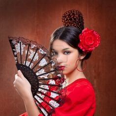 The Flamenco Fan Dancer of Barcelona Spain wears a  red rose and a black spanish hair comb