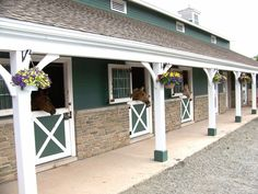 Beautiful barn, love the Dutch doors, stone, & hanging baskets horse stables Barn Stalls, Horse Stalls, Dream Stables, Dream Barn, Horse Barn Designs, Horse Barn Plans, Horse Ranch, Horse Property, Farm Barn