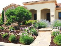 A smooth stone walkway flanked by Mediterranean landscaping leads to the entryway of this red-roofed Tuscan home with stone and stucco cladding.