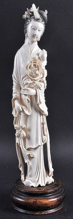 Description: AN EARLY 20TH CENTURY CHINESE CARVED IVORY FIGURE OF A FEMALE modelled in flowing robes holding a floral sprig. Ivory 12ins high.
