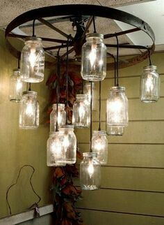 Mason Jar Lighting off Antique Wagon Wheel Barn entry Mason Jar Chandelier, Diy Chandelier, Mason Jar Lighting, Wagon Wheel Chandelier Diy, Chandeliers, Wagon Wheel Light, Wagon Wheel Decor, Jar Lights, Hanging Lights