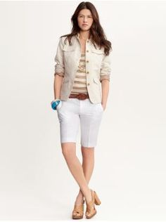 woman wearing bermuda shorts for office. she is wearing white ...