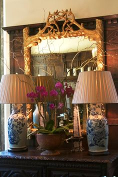 .great combination of blue/white lamps, gold faux bois mirror, floral arrangement