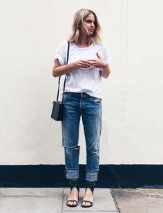 Street style look camiseta branca, calça jeans e sandália sem salto preta.