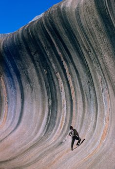 A wave of rock shaped by wind and rain towers above a plain in Western Australia, September 1963    Photograph by Robert B. Goodman
