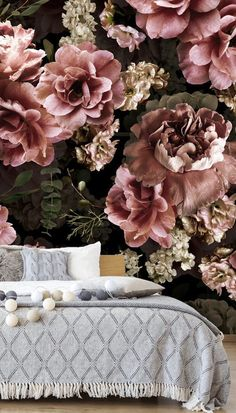 Dark floral wallpaper is a beautiful way to bring a romantic vibe into your bedroom. Choose this dark pink and green floral mural and place it behind your bed. Choose a wooden bed and headboard and style with white bedding. Add a knitted light grey blanket on top as well as grey knitted pillows and faux fur pillows to add texture. Keep all colours neutral and light to keep the room bright and paint surrounding walls in light grey or off white. Get the look at Wallsauce.com! White Bedding, Flower Making, Designer Wallpaper, All The Colors, Pink And Green, Romantic, Colours, Pillows, Floral