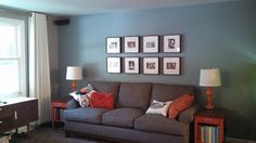 Gray living room, blue wall, gray sofa, orange accent tables, picture wall