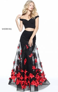 Add some sizzle to your evening in this two-piece set gown, Sherri Hill 51062. Off-the-shoulder neckline features the crop top. Sheer overlay is adorned with contrasting floral embellishments with the form-fitting lining.