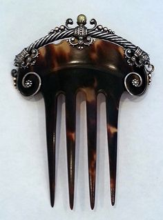 This is a Romanov comb. It is tortoiseshell, with a gold, silver, and pearl heading and the mark of one of Faberge's most famous designers.