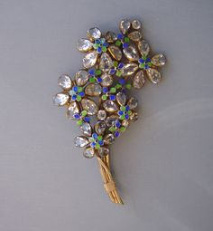 HOBE floral bouquet brooch with sparkling clear unfoiled rhinestones and petals enameled in blue, pastel blue and green, all set in gold tone wire work