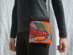 This is a beautiful shoulder bag handmade in Colombia using high quality leather and colorful Mola fabrics sourced from indigenous artisans. Made by the Kuna Indians of northern Colombia, the Mola is a textile art form unique to them and their textiles are incorporated into a variety of wearable art such as shoes, wallets, and purses. These products are made by a family run fair-trade business in Colombia. hnhlatinmarket.com