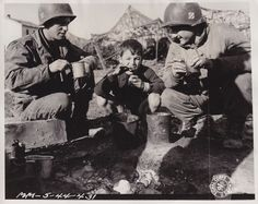 Two 3rd Infantry Division GI's share their C Rations with a local boy near Anzio.