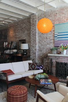 exposed brick and simple furniture lines. except the yellow lamp. Simple Furniture, Outdoor Furniture Sets, Apartment Living, Apartment Therapy, Apartment Ideas, Living Area, Living Spaces, Living Room Arrangements, Modern Light Fixtures