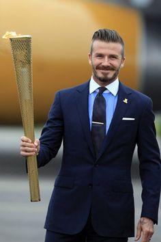David Beckham holding the olympic torch, wearing a tie pin and navy suit