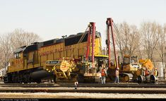 Crews from RJ Corman Derailment Services of Caseyville use two side boom tractors to lift a locomotive so a bad traction motor wheelset can be removed, at Union Pacific Railroad yards off West Chestnut Street in Bloomington, Wednesday, March 11, 2015. An idler wheel set was then put into place so the locomotive can be moved to a shop for repair. Steve Smedley photo