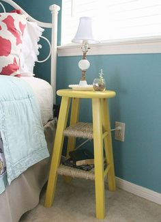 Paint an old bar stool and use it as a side table. See the full list of thrifty DIY hacks here.