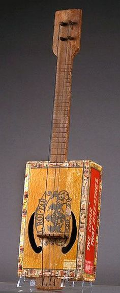 American folk art. Hand carved neck and pegs connect to a cigar box body-resonator with two clef soundholes. A wonderful artifact from about 1900.