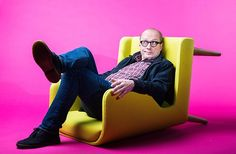 Comedian Adrian Edmondson sitting in upturned yellow chair against pink background Masters Chair, Herman Miller Aeron Chair, Cool Chairs, Bag Chairs, Man Photo, Comedians, Bean Bag Chair, Comfy, Yellow Chairs